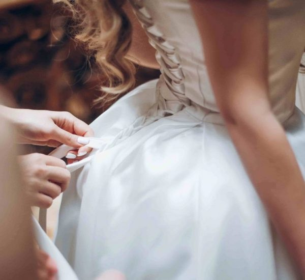 bridesmaids-dressing-bride-in-the-morning-in-hotel-qms74wd_optimized-min